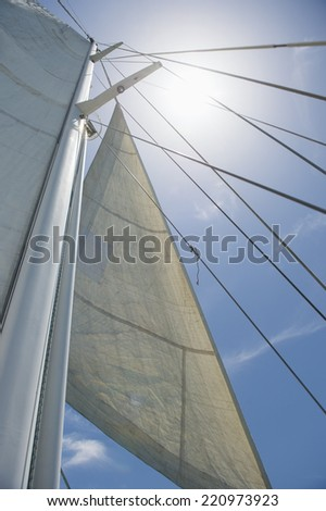 Low angle view of yacht sails and mast against sky - stock photo