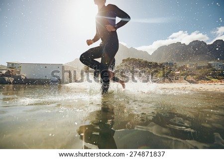 Low angle view of young athlete running into water. Participants running into the water for start of a triathlon race. - stock photo