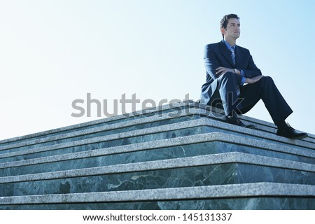 Low angle view of young businessman looking away while sitting on marble staircase against clear sky - stock photo