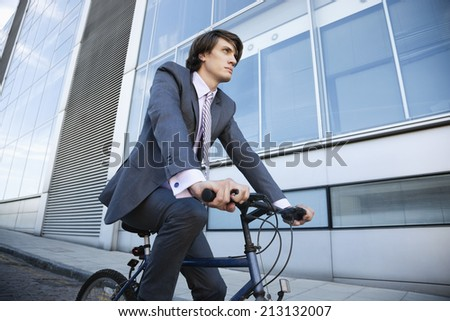 Low angle view of young businessman riding bicycle by building - stock photo