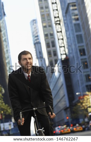 Low angle view of young businessman riding bicycle to work on urban street - stock photo