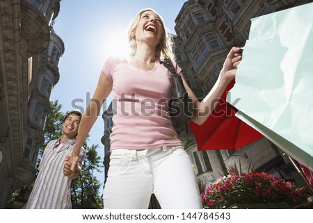 Low angle view of young couple walking down city street with shopping bags - stock photo