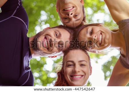 Low angle view on group of four young male and female adults with heads together in the shape of a cross looking downward with trees in background - stock photo