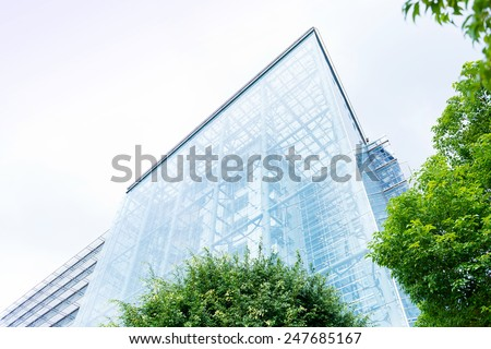 Low angle view past green foliage of the transparent glass facade of a contemporary urban skyscraper in an architectural background - stock photo