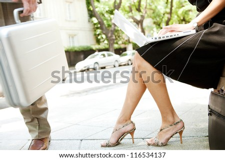 Low body section of two business people in a street scene. Businesswoman using a laptop computer and businessman walking passed holding a silver briefcase. - stock photo