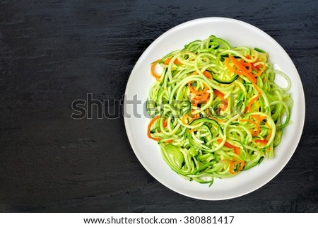 Low carb zucchini noodle dish with carrots and lime on dark slate background, overhead view - stock photo