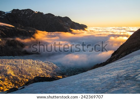 Low Clouds Blanketing the Fox Glacier at Sunset, South Island of New Zealand - stock photo