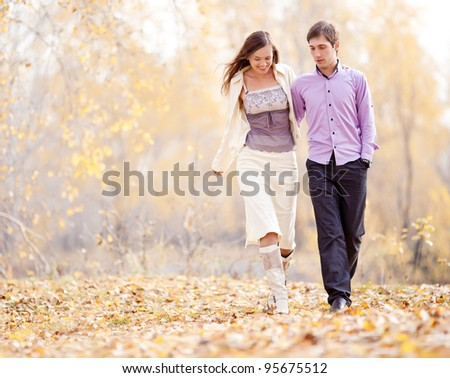 low contrast portrait of a happy loving couple walking  outdoor in the autumn park - stock photo