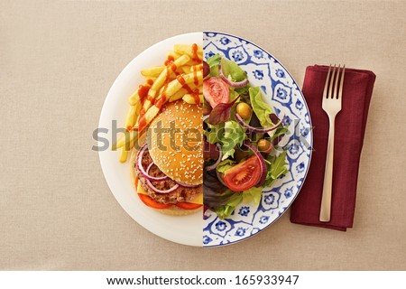 Low fat healthy salad against unhealthy greasy burger - stock photo