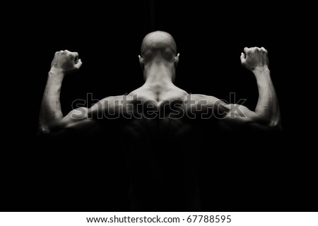 Low key artistic strong man on a black background - stock photo