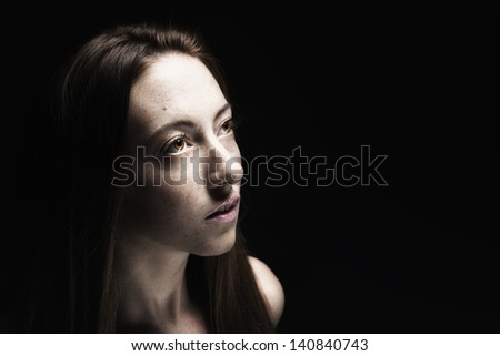 Low key desaturated portrait of young woman on black background, looking up into the darkness. Space for your text. - stock photo