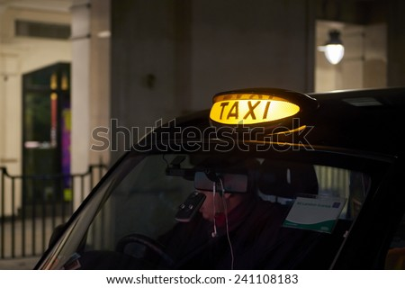 Low key detail of London black cab sign turned on at night. - stock photo