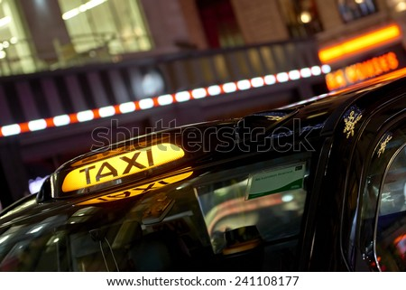 Low key detail of London black cab sign turned on at night, with shop lights in the background. - stock photo