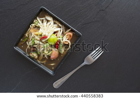 low key food background, spicy delicious papaya salad  on black tile - stock photo