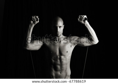 Low key image of fitness man working out with resistance bands - stock photo