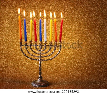 low key image of jewish holiday Hanukkah background with menorah Burning candles over golden dark glitter background  - stock photo