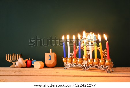 low key image of jewish holiday Hanukkah with menorah (traditional Candelabra) and wooden dreidels spinning top over chalkboard background, room for text  - stock photo