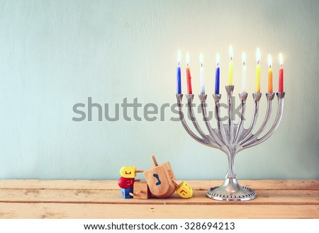 low key image of jewish holiday Hanukkah with menorah (traditional Candelabra) and wooden dreidels (spinning top)  - stock photo