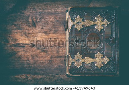 low key image of top view of antique book cover, with brass clasps. vintage filtered and toned