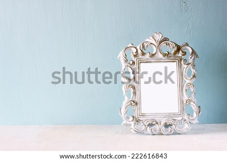 low key image of vintage antique classical frame on wooden table. filtered image - stock photo