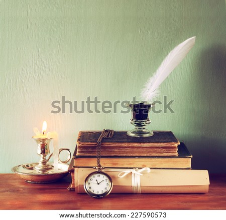 low key image of white Feather, inkwell, scroll ancient books on old wooden table - stock photo
