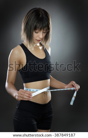 low key lighting of a woman using a tape measure around her waist - stock photo