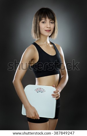 low key lighting of a young slim woman holding scales shot in the studio on a gray background - stock photo