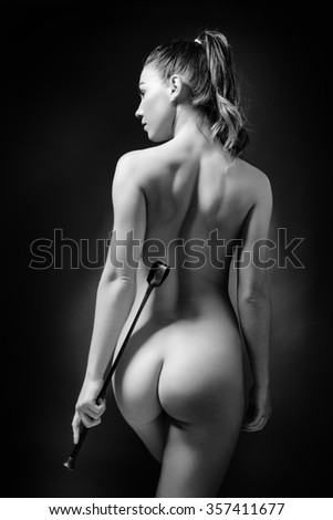 low key lighting of the back of a sexy woman holding a whip - stock photo