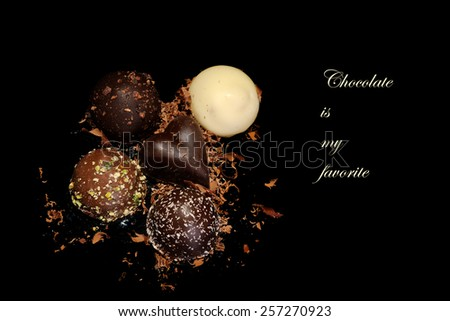 Low Key lighting on Chocolates sitting on a reflective black background and space for your text - Chocolates are my favorite - stock photo