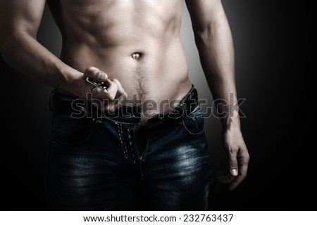 Low key. Man showing his muscular body. Stripper unzips jeans and belt. - stock photo