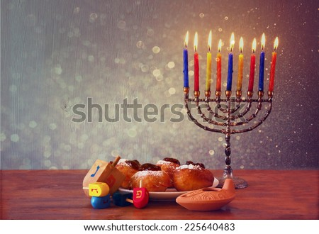 low key of jewish holiday Hanukkah with menorah, doughnuts and wooden dreidels (spinning top). retro filtered image - stock photo