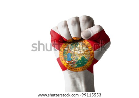 Low key picture of a fist painted in colors of american state flag of florida - stock photo