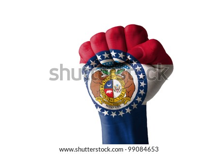 Low key picture of a fist painted in colors of american state flag of missouri - stock photo