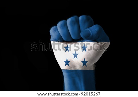 Low key picture of a fist painted in colors of honduras flag - stock photo