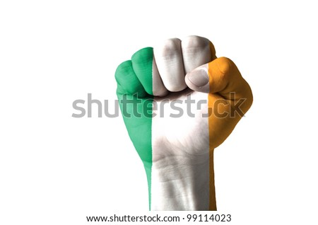 Low key picture of a fist painted in colors of ireland flag - stock photo