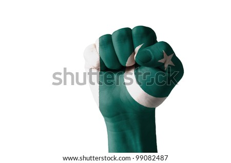 Low key picture of a fist painted in colors of pakistan flag - stock photo
