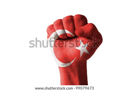 Low key picture of a fist painted in colors of turkey flag - stock photo