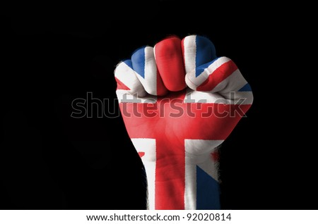 Low key picture of a fist painted in colors of united kingdom flag - stock photo