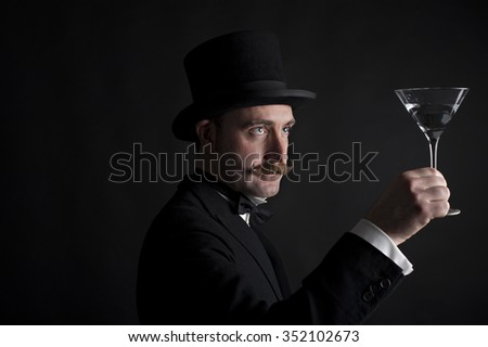 Low key portrait of a Victorian gentleman examining his cocktail glass. He is wearing a top hat and bow tie and has a groomed mustache. - stock photo