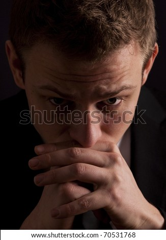 Low key portrait of a young businessman in deep thought, worrying or even praying. - stock photo