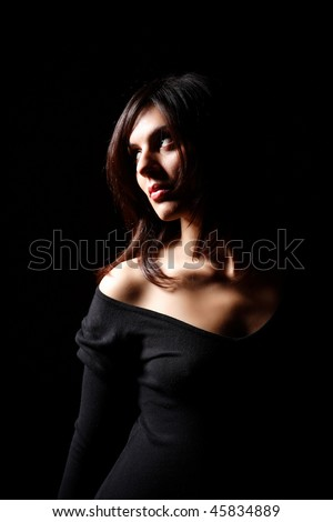 Low key portrait of a young woman with side lighting - stock photo