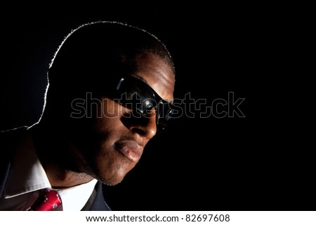 Low key portrait of an African American business man dressed in a suit and sunglasses standing in front of a dark black background. - stock photo