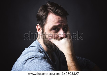 Low key portrait of man sitting in dark and contemplating - stock photo