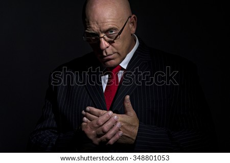 Low key portrait of mature male in pin strip suit wearing glasses and rubbing his hands together. He can either be a criminal boss or no nonsense CEO - stock photo