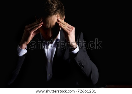 Low-key portrait of modern serious business person in dark suit sitting at office desk looking down and contemplating with both hands resting at head, isolated on black background with copy-space. - stock photo