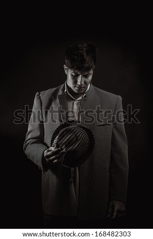 low key portrait of young gangster with hat in the darkness. Sepia toning. - stock photo