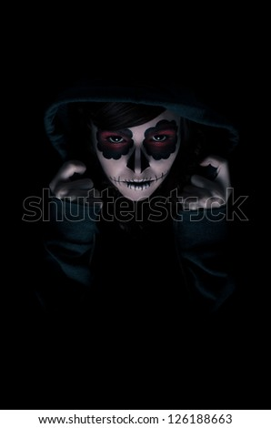Low key portrait of young woman with sugar skull make-up - stock photo