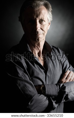 Low Key Shot of a Handsome Senior Man against Dark Background - stock photo