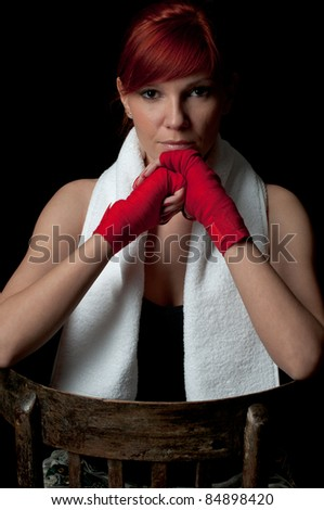 Low-key studio portrait of a serious red-haired young woman in boxing-bandage meditating before the fight - stock photo