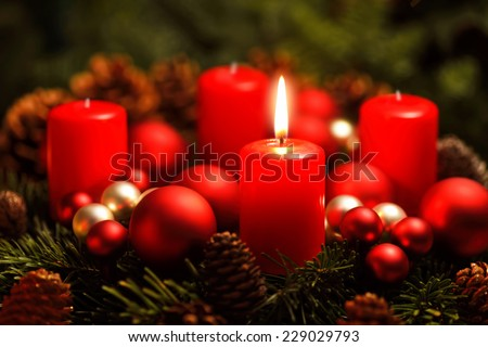 Low-key studio shot of a nice advent wreath with baubles and one burning red candle - stock photo